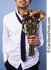 Young man with withered flowers