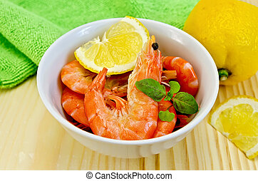 Shrimp in a white bowl with lemon slices - Raw shrimp in a...