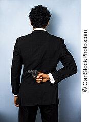 Businessman hiding gun behind his back