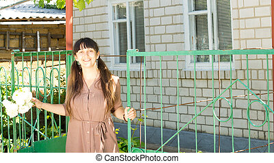 Middle age woman standing in the gate of her house