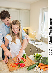 Young couple chopping peppers