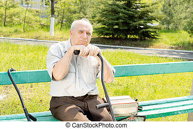 Senior man outdoors - Portrait of senior man sitting on the...