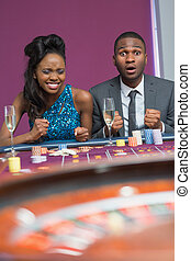 Couple sitting at roulette table wa