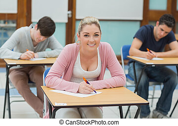 Writing students in a classroom - Three students sitting at...