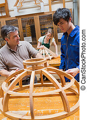 Teacher and a student in a woodwork - Teacher and student at...