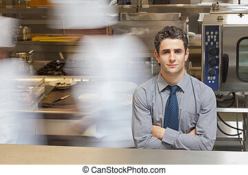 Waiter standing in busy kitchen - Smiling waiter standing in...