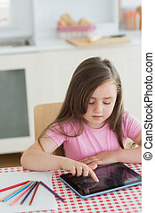 Young girl using tablet computer sitting at kitchen table
