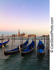 Gondolas at sunset with San Giorgio di Maggiore church,...