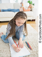 Little girl sitting at the floor drawing