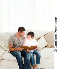 Father and son reading a fairy tale in the living room