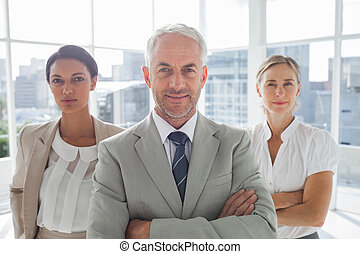 Confident businessman standing in front of colleagues with...