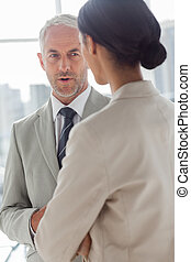 Concentrated businessman listening to female colleague in...