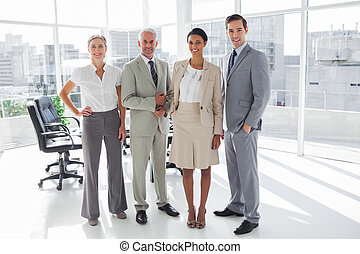 Smiling business people standing in line in the meeting room