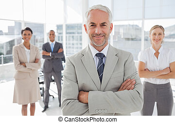 Businessman with arms folded standing in front of colleagues...