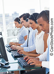 Call center employees sitting in line in a workplace