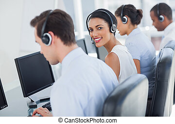 Smiling call centre employee looking over shoulder while...