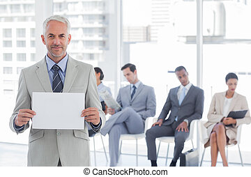 Smiling businessman holding a blank sign