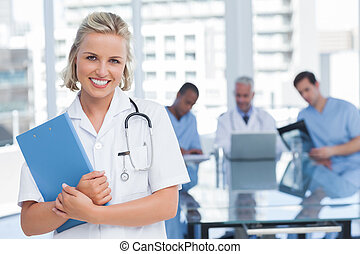 Smiling nurse holding file in office