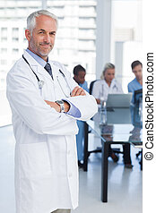 Doctor with arms crossed standing in front of medical team