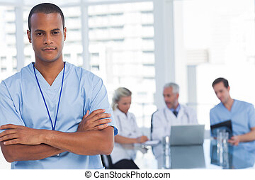 Serious doctor with arms crossed standing in front of his...