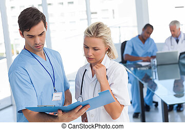 Two doctors examining a file in front of medical team