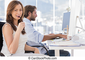 Woman biting her glasses with colleague working behind in...