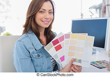 Interior designer holding up colour samples and smiling at...