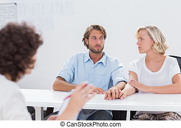 Couple looking doubtful during therapy session as therapist...