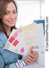 Cheerful interior designer holding up colour samples close...