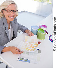 Cheerful blonde interior designer holding colour charts