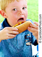 Licking Mustard and Ketchup - Young boy licking mustard and...