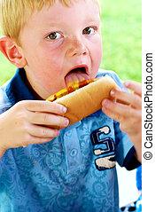 Licking Mustard and Ketchup - Young boy licking mustard and...