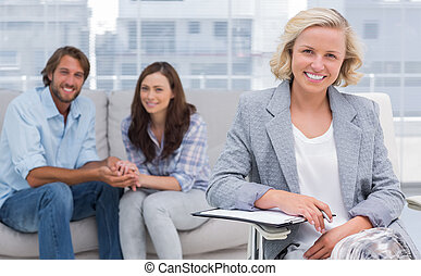 Smiling couple and therapist looking at the camera