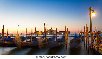 Gondolas at sunrise with San Giorgio di Maggiore church,...