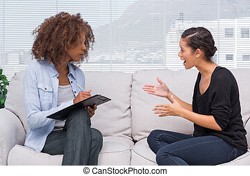 Upset woman speaking to her therapist while she is taking...