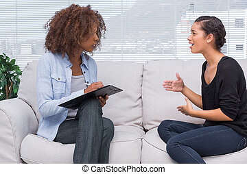 Woman gesturing and speaking to her therapist who is taking...