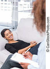 Woman laughing on sofa during therapy session