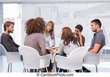 Patients around therapist in group therapy session -...