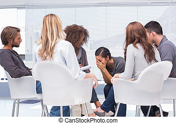 Therapist listening a woman crying during group therapy