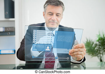 Businessman using futuristic touchscreen to view social...