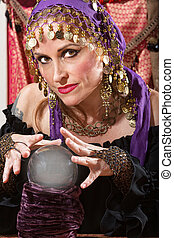 Waving Over a Crystal Ball - Pretty lady waving hands over...