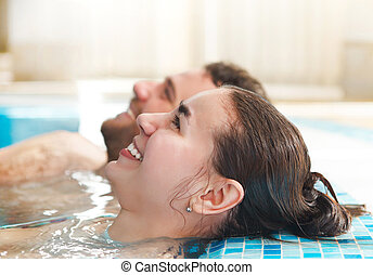 Young couple relaxing in water in a spa resort - Young happy...