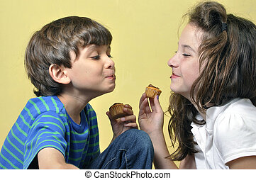 Fun with cupcakes - Little boy and girl have fun acting...
