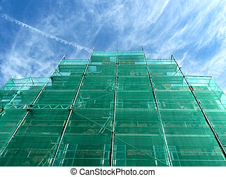 green scaffolding under blue sky