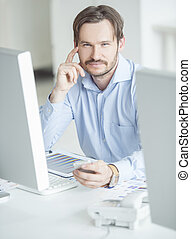 Businessman sitting in front of computer monitors