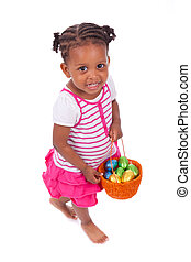 African Asian girl holding chocolate ester egg, isolated on...