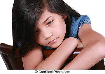 Sad nine year old girl sitting on chair, bored