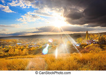 Russian landscape autumn hills and village below, glare of sun through clouds, Russia Volgograd