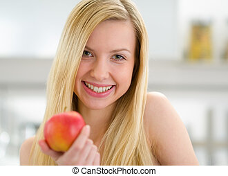 Portrait of smiling teenager girl with apple in kitchen