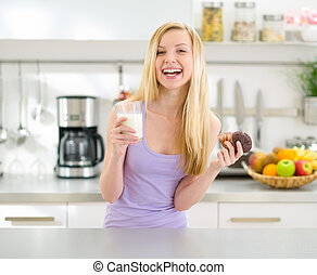 Happy teenager girl eating chocolate muffin with milk